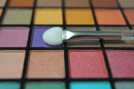Close up colorful eyeshadow palette. Focus on the make up applicator.