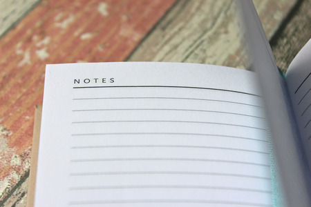 Open blank Notes page of diary, close up on rustic wooden background.