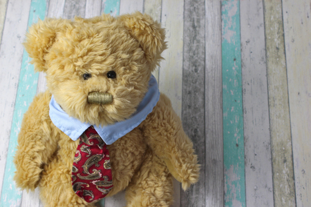 Office teddy bear dressed in shirt and tie against a rustic wooden background. Stock Photo
