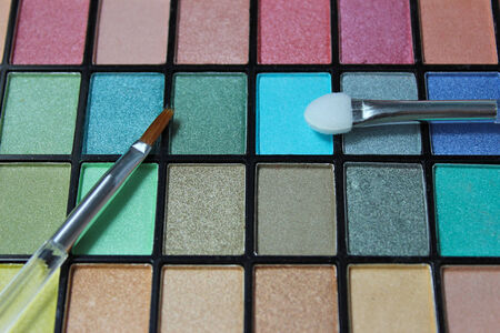 Colorful eyeshadow powder palette with focus on make up applicator.
