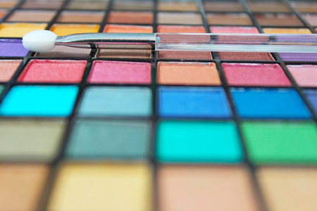 Vivid and colorful make up palette and applicator. Focus on the applicator wand. Stock Photo