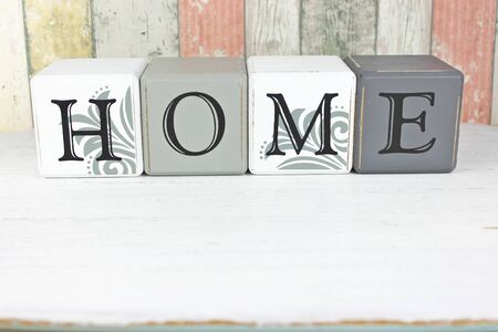 Home sign made from blocks on a distressed wood background Standard-Bild