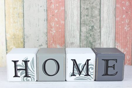 Blocks spelling the word 'Home' on a distressed wood background. Standard-Bild