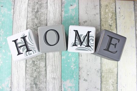 Home sign made of blocks on a distressed wood background with turquoise tones. Standard-Bild