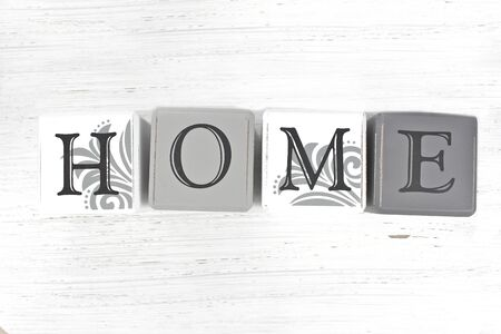 The word Home spelled with blocks on a distressed wood background.