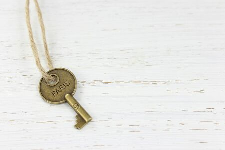 Brass key stamped wit the word Paris on a white distressed wood background. Stock Photo