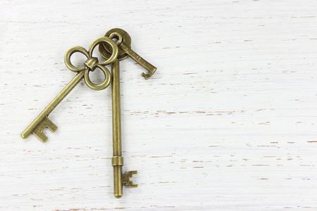Three brass keys on a white distressed wood background. Copy space. Stock Photo