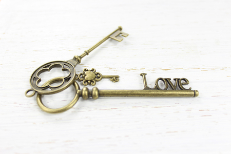 Three brass keys on a white distressed wood background. One key is fashioned with the word Love. Stock Photo
