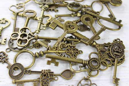 Pile of antique brass keys on a distressed white wood background.