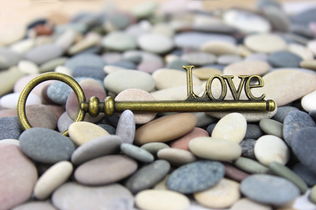 Love Key on a beach stone  pebble background. Great Valentines background. The key to Love.
