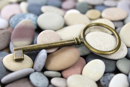 Old Brass lying key on a pebble beach. Macro. Stok Fotoğraf