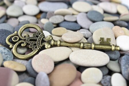 Old Brass key laing on beach stones on a pebble beach