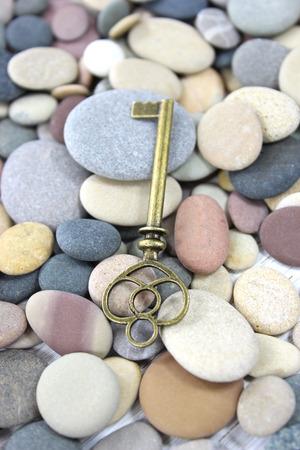 Antique brass key lying on pebbles beach stones on the beach.