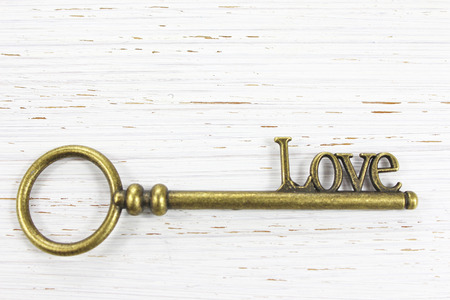 The key to Love. Antique brass key with the word Love on a white distressed wooden background. Copy space.