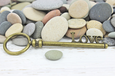 Antique Key to Love on a beach stone background with white distressed wood.