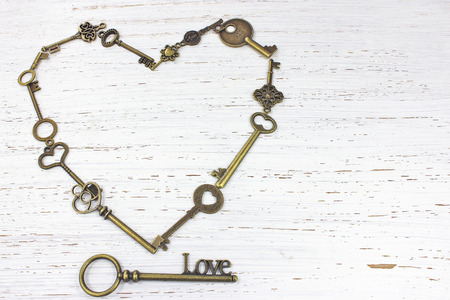 Heart shape of keys with key to Love on a white distressed wood background.