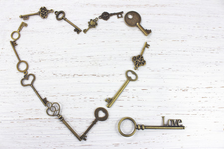 Heart shape made with old antique keys. Valentines day concept on a white distressed wood background. Standard-Bild
