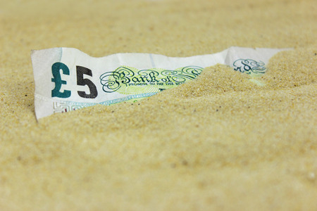 UK Five Pound note covered in sand. Travel Insurance. Money lost on beach.