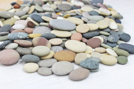 Pebbles on a white wooden background