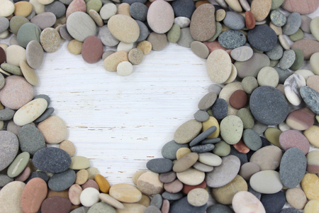 Heart shape made with colorful pebbles on a white distressed wood background.