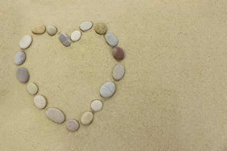 Beach stones in the shape of a heart on a sandy beach background. Stock Photo