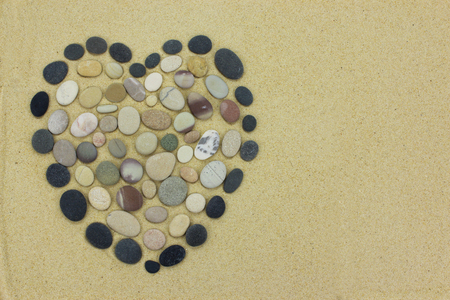 Heart shape made from beach stones or pebbles on golden sand.