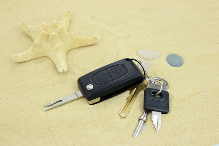 Keys on the sand with starfish