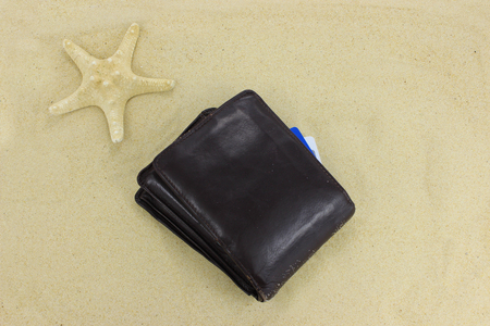 Brown leather wallet on sandy beach Stock Photo