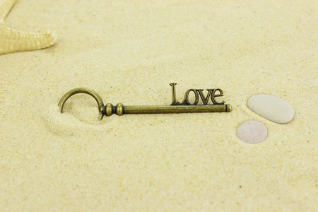 Brass key with the word Love on it lying on a sandy beach.
