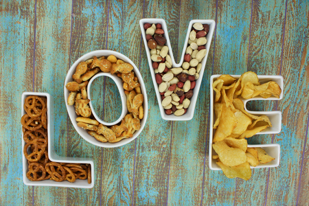 Snacks in Love shaped letter bowls on rustic turquoise wooden background
