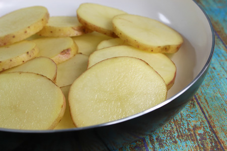 Close up of potato slices in a white pan on a rustic wooden background. Standard-Bild