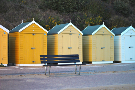 beach huts: Bench in front of Shades of yellow Beach huts in a row at the seaside. Focus on bench.