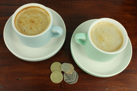 English Coins with two cups of coffee on a dark rustic wooden table.