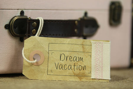Paper tag with the handwritten words 'Dream vacation' on vintage suitcase.