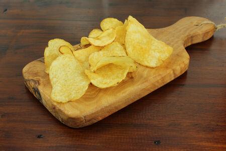 Rustic Potato chips or crisps on a dark wooden background