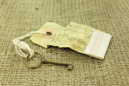 fulfilment: Key with a paper tage and the handwritten word happines. Key to happiness concept on rustic background Stock Photo