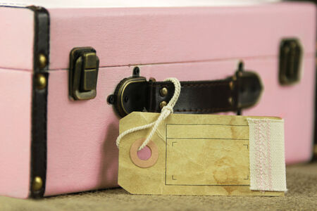 Pink retro vintage suitcase with blank paper tag and copy space.
