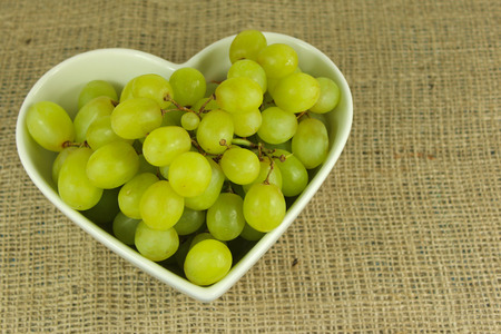 Green grapes in a white heart shaped bowl on a rustic hemp background.