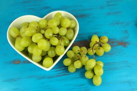 Green grapes in heart shaped bowl on a turquoise distressed wood background. Focus on grapes in bowl. Stock Photo