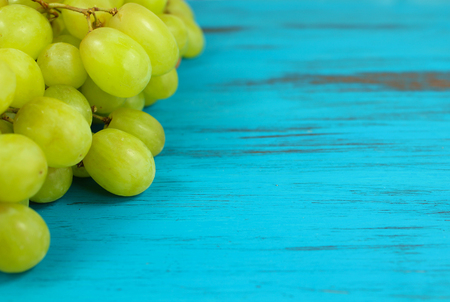 Close up of Bright green grapes on a turquoise distressed wooden background