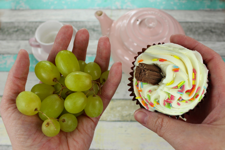 Healthy grapes or cupcake? Hands holding a healthy snack of grapes in one hand and an unhealthy cupcake in the other. Tea items in background.