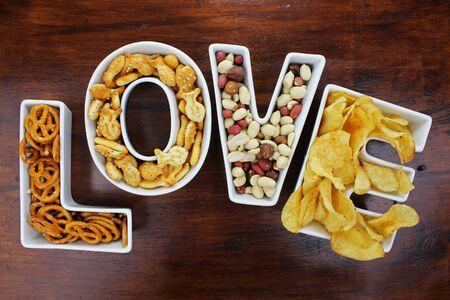 Love snacks Snacks in Love letter bowls on dark wooden background