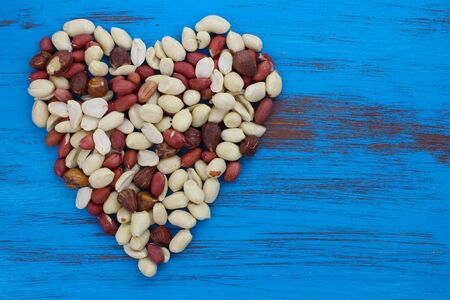 peanuts nuts in a heart shape on blue rustic distressed wood background.