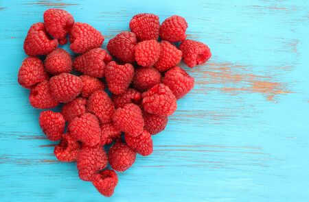 red raspberries in a heart shape on blue wooden background
