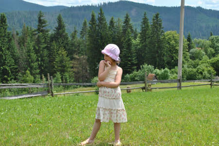 vested: small rural girl on meadow on background wood