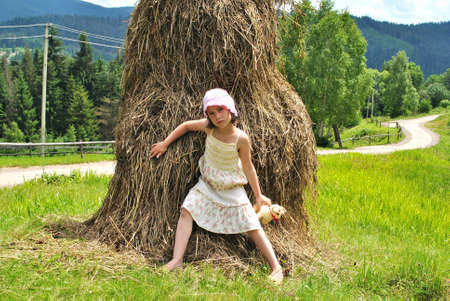 vested: girl sits around stack network on meadow.