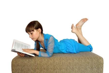 niña: Chica tumbada en el sofá leyendo un libro