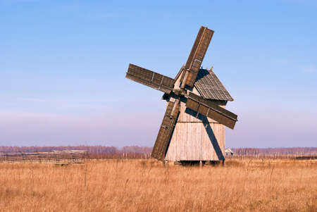 Wooden windmill in the field against the blue sky on a sunny day. photo
