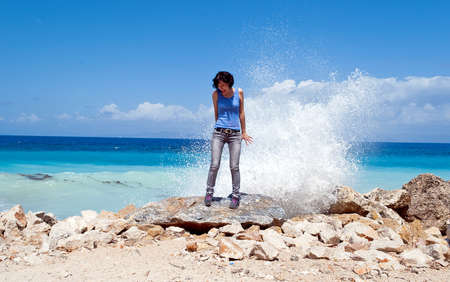 girl standing under the spray of waves on the sea shore of the island of Rhodes photo