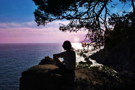 bewonderen: silhouette man sits on top and admire the sunset and the sea